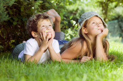 Boy and girl (6-9) lying on grass, looking up